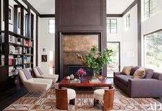 In the double-height family room, the bronze-clad fireplace is surrounded by vintage Gianfranco Frattini lounge chairs | archdigest.com