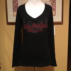 "Harley Davidson V-Neck Rhinestone Studded Shirt This is a pretty v-neck long sleeve shirt from Harley Davidson.  It has the Harley Davidson Motorcycles logo in red with rhinestones on the front, and  ""Zepka"" Harley Davidson Johnstown, PA in red on the back.  It is a size small and measures 23"" from shoulder to waist & approx. 16"" from armpit to armpit.  The sleeves have zippers on the wrists & measure approx.  23"" from shoulder to wrist.  Made of 95% cotton & 5% spandex, it has been worn…"