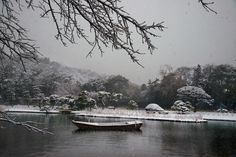 Steve McCurry - Yokohama, 2014. A boat covered in snow, floating in a pond.