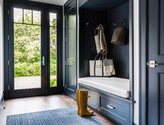 Dark Blue Mudroom. Dark blue mudroom features a dark blue built in bench fitted with drawers placed under a dark blue backsplash lined with hooks flanked by dark blue closet doors. #Mudroom #darkblue #navy Alisberg Parker