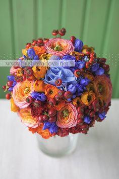 Яркий свадебный букет из оранжевых ранункулюсов с ягодами шиповника и голубой гортензией