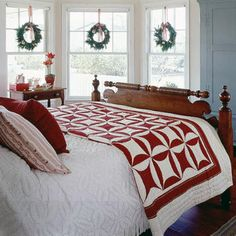 red and white quilt; country bedroom, brown furniture, bed; white bedspread layered with cheery quilt; fun wreaths on windows! blue armoire; darken our bedroom suite w/ stain?