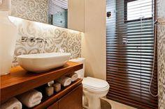 O lavabo também faz papel de banheiro para o quarto de hóspedes, por isso os arquitetos Débora Dalanezi e Marcello Sesso optaram por esconder o boxe de uma forma diferente. Do tamanho exato do vão do boxe, uma persiana em madeira esconde a parte do chuveiro quando necessário – quase como se fosse um papel de painel em madeira.