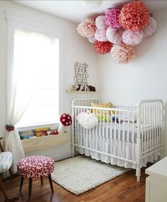 I love the poms and the bookshelf below the window in this nursery