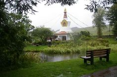 Samye Ling. There are seats, benches and rocks to sit on. There is a Buddha image under a Chinese-style canopy. Candle-lanterns hang from the corners of the canopy.   From the trees hang windchimes, prayerflags and candle-lanterns. Together with the rocks and surrounding pond, the four elements are well represented.