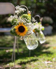 Simple but beautiful ceremony flowers lining the walkway of our country / rustic wedding. Sunflowers and baby's breath in mason jars with jute twine hanging from a simple garden hook.