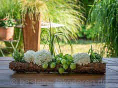 Sommerliche Blumen- Tischdeko selbst gemacht aus einer Baumrinde, alten Flaschen und Gläsern mit Blumen und Gräsern befüllt. Der Sommer ist wohl die beliebteste Jahreszeit. Sommer und Sonne, das verspricht gute Laune, Zeit für Essen im Freien, Grillfeste...... und so mancher lauer Sommerabend wird für ein spontanes Treffen mit der Familie und Freunden genutzt.