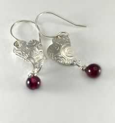 Fine silver earrings that hand approximately an inch down from the ear. The measure a little less than 1/2 at the widest part of the earring. The dangle stone is a garnet.