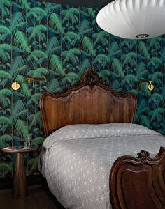 The jungle wallpaper is by Cole & Son. Warner found the vintage bed on Krrb; the lamp is by George Nelson. Photo: Floto + Warner