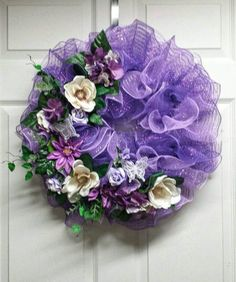 This purple spring mesh wreath would be a great addition for your front door. It is made with high quality deco mesh and adorned with various flowers, and a hand made bow. This wreath measures approximately 22 in diameter.