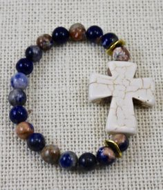 Cream howlite cross and orange and blue sodalite beaded stretch bracelet.  This listing is for 1 item. Please allow 2 business days for processing time, not including shipping times.  This bracelet fits most standard 7 inch wrists. I can make this bigger or smaller if you feel you need a different size, or would like a specific fit.  Please read all details about the listing and shipping information before making your final purchase.  Right now, I am only making 1 of each bracelet design. If…