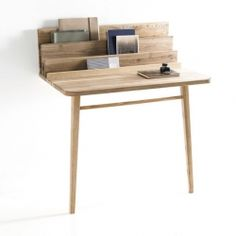 The piece is a hybrid workspace and console table with built in storage. Leaning against the wall, the desk is minimal and light.