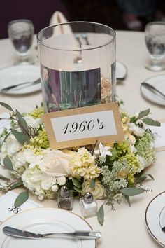 50th anniversary table centerpieces: each table was a decade; there were glass cylinders filled with photos from that decade and gold-foil-wrapped chocolates, surrounded by flower wreaths