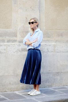 Jessie Bush from We The People wears a chambray blue shirt, a pleated metallic blue midi skirt and white sneakers.