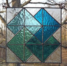 This handcrafted Stained Glass Suncatcher Panel is an adaptation of the traditional Card Trick Quilt Square Pattern.    The stained glass quilt block panel measures 8 inches square, is constructed in the traditional Tiffany style from various textures and hues of Teal and Aqua stained glass. The background is done in a textured clear glass that lends a fabric feel to the piece. This suncatcher quilt block panel is finished with an antique patina has two handcrafted loops and a length of…