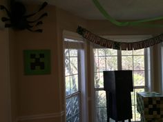 I used a green tablecloth from the Dollar Store to cover the pictures I had in my dining room, then used a large black marker to draw a creeper face.