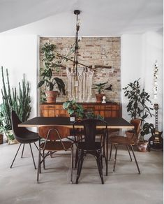 A dining area with white and exposed brick walls and danish vintage furniture.