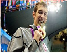 IMG311a: National swimmer, Michael Phelps, displayed on ESPN in a positive image while he holds up a gold medal which is clearly the center of the picture. The American flag is absent from the image because he is so highly recognized. american flag, michael phelp, swimmer