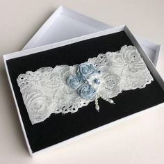 This beautiful lace bridal garter is made with soft white stretch lace, and embellished with three small blue roses, blue and ivory beads, and a smokey blue crystal. Two short strands of beads dangle tantalisingly from the floral arrangement, moving gently with your body. With the small blue flowers and beads, it would make a lovely Something Blue worn by the bride on her big day. This lace wedding garter lies flatter against the skin (except where the flowers are positioned) and is less…