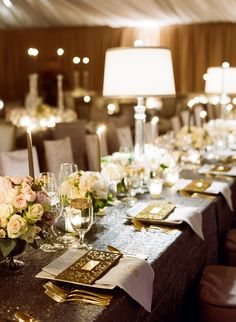 Since the couple's wedding was held on New Year's Eve, the decorations were sophisticated and sparkling. Charcoal sequin linens topped long tables, which were decorated with gold-rimmed glassware and ivory centerpieces. Photography: Liz Banfield and Adrienne Page. Read More: http://www.insideweddings.com/weddings/glittering-gold-new-years-eve-celebration-in-oklahoma-city/614/