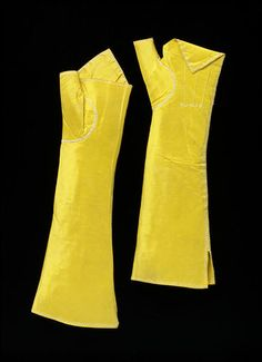 A pair of women's elbow-length mittens in yellow taffeta with gusset thumb and a point at the back of the hand. The seams are embroidered over in herringbone stitch with white silk. The points are raised with outline stitch in white silk. Great Britain, 1780-1800