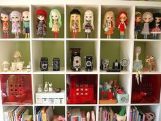 Blythe dolls and camera collection being displayed in an Ikea Expedit bookcase