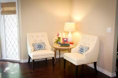 A pair of white transitional chairs with button-tufted seat backs anchor one corner of this living room. Blue and white Suzani-print pillows bring patterned pop to the color scheme.