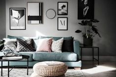 Modern Scandinavian living room with a green velvet couch and green plants.