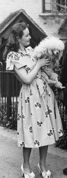 Actress Patricia Roc (and a preciously adorable shaggy friend) looking cute as a button in a cotton bow print Horrockses summer dress.
