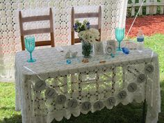 table with crocheted tablecloth behind, chairs have organza covers with rhinestones. Tablecloths from Nanalulus Linens