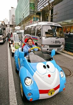 """A single-seat electric vehicle, shaped like the Japanese cartoon character Doraemon and produced by Japanese toy giant Takara, is driven in front of the newly opened shopping mall """"Coredo Nihonbashi"""" in downtown Tokyo, 30 March 2004. The vehicles are priced at 10,000 USD each. AFP PHOTO / Yoshikazu TSUNO"""
