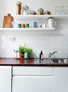 white subway tile + wood countertop + open shelving