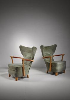 A pair of very rare and spectacular Finnish wingback lounge chairs from the late 1940s, attributed to Runar Engblom.  The wooden armrests are wrapped with a leather cord. The chairs have previously been reupholstered with a green alcantara.  The chairs were designed for and used in Hotel Vaakuna, Helsinki. The building was designed by architect Erkki Huttunen in 1947. Paavo Tynell designed the lighting of the hotel and Engblom did the furnishing.