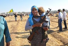 TURKEY. Bakur (Northern Kurdistan). Sanliurfa province. Near Pirsûs/Suruc. September 26, 2014. A Syrian Kurdish woman holds an AK-47 and a child on the Turkish side of the Syrian border after refugees...