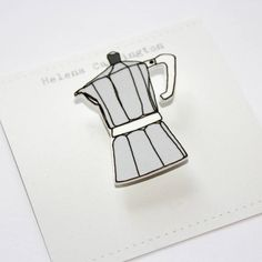 A quirky espresso pot brooch.Perfect for any coffee lover, this brooch is made from an original illustration of an Italian espresso pot, digitally printed onto plastic with a matte finish. In a traditional silver grey colour, the brooch comes pinned onto a little card ready to give as a gift. The espresso pot design is also available as cufflinks!Made from plastic. The brooch measures approx 4.5cm high. Each one is handmade so will vary slightly.