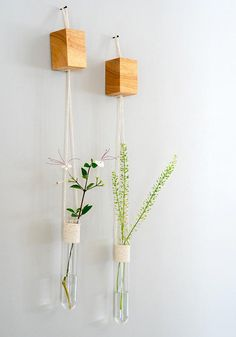 Those hanging vases is a set of 2 wall tube vases. Those glass hanging vases is a beautiful pair of hanging vases that are perfect for a mothers day gift. A set of 2 hanging vases wrapped and attached to a solid oak cube. Pure and simple presence. Perfect for your kitchen, living
