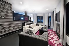 A hot pink rug adds a bold accent color in the middle of this gorgeous black and white living room. A striped wall adds pattern and movement to the open design. A gray leather tufted chair and sleek white leather sectional create seating around a polished black coffee table, black framed fireplace and mounted TV.
