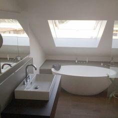 Eine freistehende Badewanne unter einem Dachflächenfenster