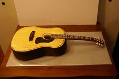 Acoustic Guitar Cake - Well this one is pretty strait forward although i was pretty nervous making it. I found a clipart picture online and used that to make a template for the body of the guitar. The neck was foam-board covered in chocolate fondant (which i marbled with some tan fondant). the decorations are all fondant. The tuning pieces are fondant stuck unto toothpicks pushed through the foamboard. I don't know if you can see from my picture but i tried to get that wood grain into the…