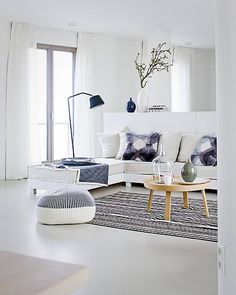 Scandinavian living room - love the striped rug and ottoman.