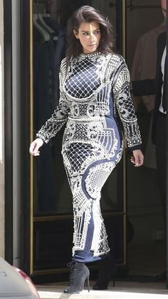 Kim showed off her figure in a body-hugging navy blue Balmain dress that featured intricate silver beading. She finished the look with black high-heeled booties.