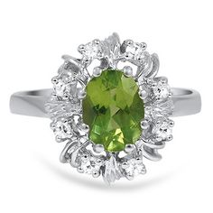 1950s Engagement Ring. A vivid green oval cut peridot is lofted high and center set in an eight prong crown style setting while surrounded by a glittering halo of accent diamonds for a distinctive and dazzling Retro-era ring (approx. 0.16 total carat weight).