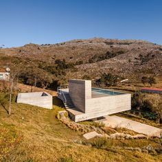 A narrow swimming pool spans the roof of this concrete residence in northern Portugal, designed by Carvalho Araújo to exploit views of the rugged landscape