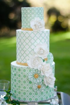 St. Patrick?s day inspired cake. My favorite part of creating themed cakes is just tiptoeing around the concept rather than being too literal. So with this one I used a traditional quatrefoil pattern that reminded me of four leaf clovers and stuck with a simple green, white & gold color palette. The bold modern geometrics were softened by the the rice paper pinwheels and gumpaste gardenias.