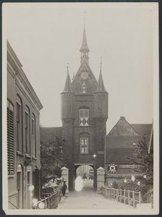 De #Lekpoort in #Vianen, 1933. De Voorstraat is door de Lekpoort te zien. Er is een Nederlandse vlag te zien en een legervoertuig?