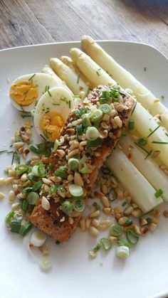 Gestoomde asperges met gebakken zalm. Ingrediënten: asperges, zalmmoot, bosui, pijnboompitjes, verse knoflook, zwarte peper, roze himalayazout, ei, bieslook, sesamolie.