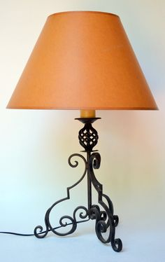 Mid 20th century Spanish Revival iron candlestick lamp glows amber through the aged paper shade. It's in my Etsy shop.
