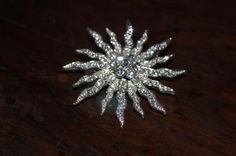 Classic white rhinestone starburst brooch  This sparkler definitely attracts attention.  Nothing like statement jewelry!  Classy, classic, and sparkling like only faceted stones, this brooch is the perfect accompaniment to a little black dress, or whatever outfit you need to dress up.  approx 5.5 cm in diameter   Brooch is part of my personal collection, and is currently for sale!