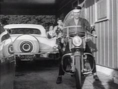 Elvis, taking his motorcycle out for a spin, as a crowd of fans and neighbors watch him go. Audobon Drive, 1956..@Wertheimer