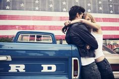 An old Ford truck. Cool guys in leather jackets and blue jeans with their girlfriends. An American flag background. This picture screams 'Classic America'.